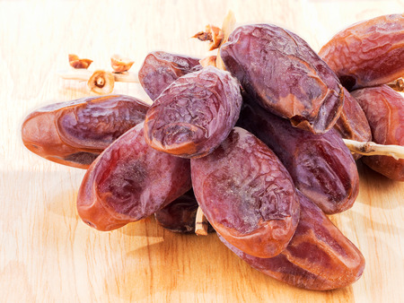 date fruit: sweet dry date fruit isolated on wooden background Stock Photo