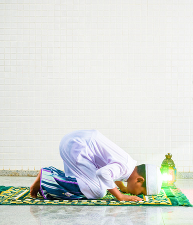 skull cap: Muslim child worships and prays for Allah(muslims God) , the prostate gestures are performed on carpet on the mosque floor