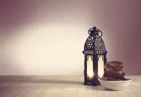 dateert fruit op een witte schotel op houten vloer in de buurt van glanzende lantaarn op kleurrijke achtergrond, klaar om te serveren in de ramadan kareem nacht.