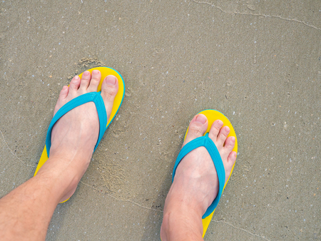 footware: human bare feet standing on the flip-flop sandal footware, on the sea beach Stock Photo