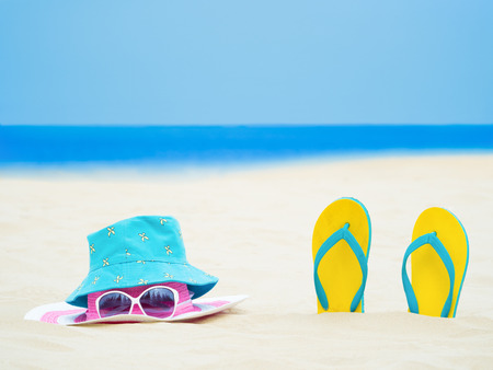 sandal footware, straw hat, and sun glasses on the sand beach