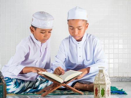 Aziatische moslim kinderen met een glimlach gezicht te lezen van de heilige Koran (het publiek post van alle moslims).