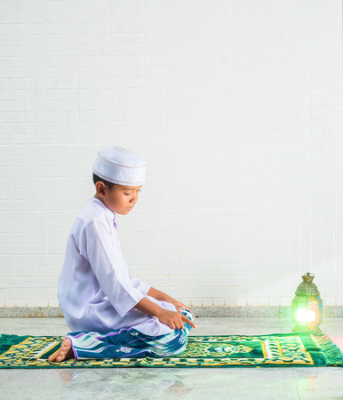 reciting: Muslim child worships and prays for Allah(muslims God) , the prostate gestures are performed on carpet on the mosque floor