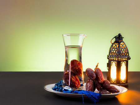 arabische letters: Date palm fruit drink called nabis, and Rosary with arabic letters of name of Muslim God Allah , and lightened Lantern by candle