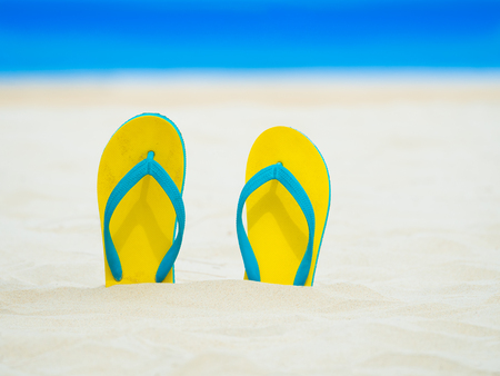 footware: yellow flip-flops sandal footware in sand on the beach in thailand.