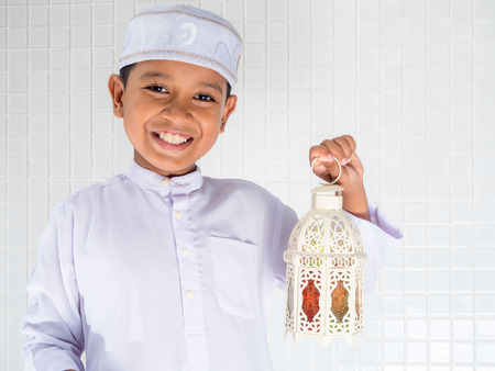 muslim children in traditional dress holding white lantern with smile face Stock Photo
