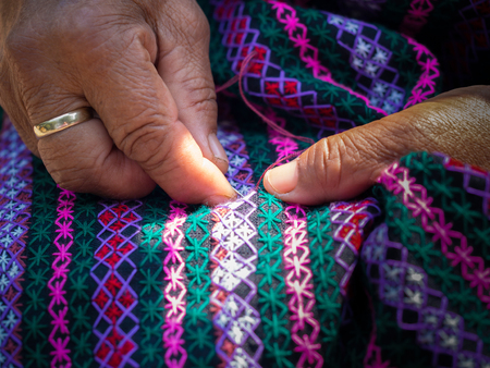 flathead: old womans hand sewing on crafting cloth, traditional homemade fabric with needle and thread