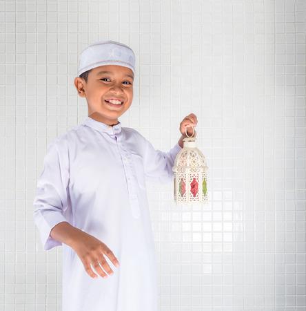 moslimkinderen in traditionele kleding die witte lantaarn met glimlachgezicht houden Stockfoto