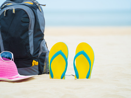 footware: backpack, sandal footware, straw hat, and sun glasses on the sand beach Stock Photo