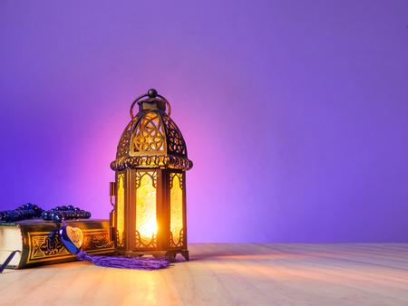 """kaarslicht van de lantaarn moslim stijl van schijnt op Arabische letters van de naam van de islamitische God """"Allah"""" in hartvorm met heilige boek Koran. Stockfoto"""