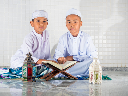 Asian muslim children with smile face read the holy Quran(the public item of all muslims ).