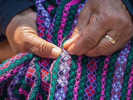 crafting: old womans hand sewing on crafting cloth, traditional homemade fabric with needle and thread