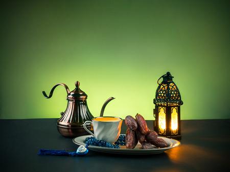"""Dadelpalm fruit drankje genaamd """"nabis"""", en Rozenkrans met Arabische letters van de naam van de islamitische God """"Allah"""", en verlichte lantaarn door kaars Stockfoto"""