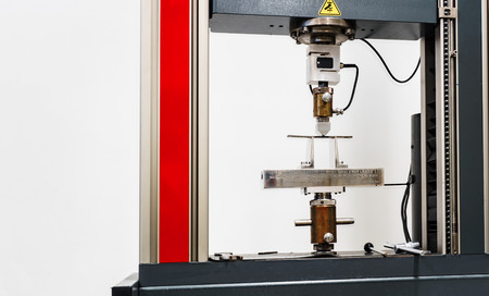 specimen testing: engineering tensile strength machine in testing process, close up on test specimen Stock Photo