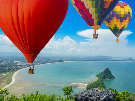 beautiful sea shore on the tropical summer time, showing blue sky, cloud and wave in the high elevated view with hot air balloons
