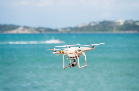 phantom: SURATTANEE, THAILAND - SEP 11, 2015: Photo of DJI Phantom quadrocopter drone in flight against a blue sky. DJI Industries makes a wide range of UAVs for recreation and business.