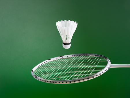 shuttlecock: badminton ball and racket on green background