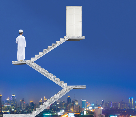 door opening: Concrete stairway leading to exit door opening to blue sky, to evening sky and night sky, with Muslim boy standing on stairs Stock Photo