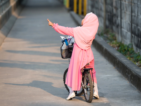 petite fille musulmane: happy muslim girl with full hijab in pink dress , asian traditonal style dress