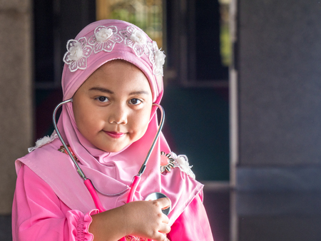 petite fille musulmane: happy muslim girl with full hijab in pink dress , asian traditional style dress, playing strethoscope.
