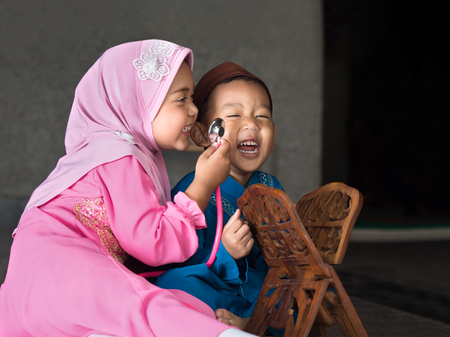 happy muslim girl with full hijab in pink dress , asian traditonal style dress playing with her brother inside mosque.