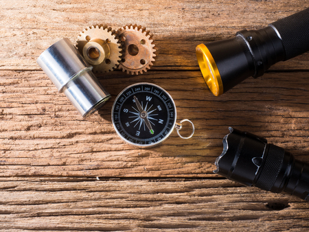 compass and flashlight placed on wooden background, equipment for travel and expedition