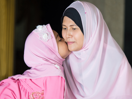 petite fille musulmane: happy muslim girl with full hijab in pink dress , asian traditional style dress Banque d'images