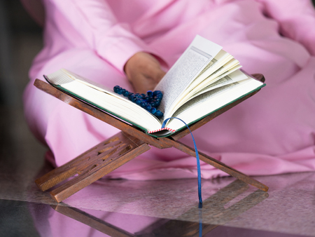 petite fille musulmane: happy muslim woman with full hijab in pink dress , asian traditional style dress, reading the holy Quran book