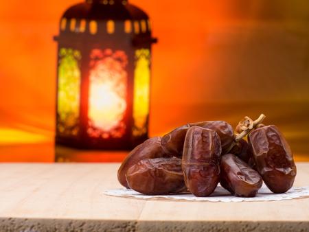 Candle light lids on muslim styles lantern shining on date fruits, use as greeting on ramadan kareem mubarak Stock Photo