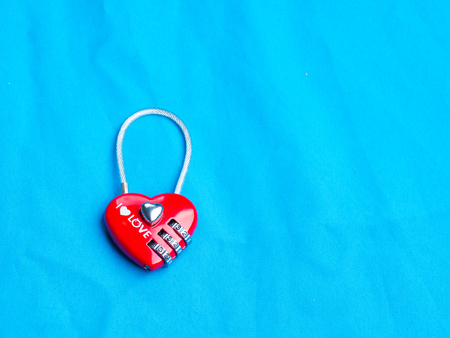 red heart shape of the key lock with encrypting numbers on cloth background