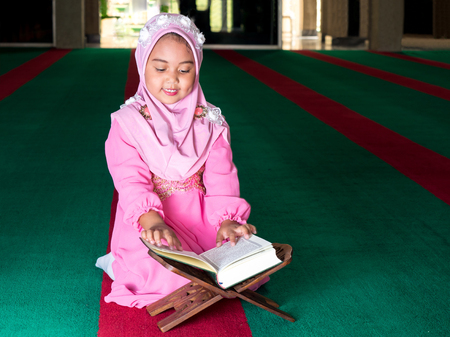 happy muslim girl with full hijab in pink dress , asian traditional style dress reading the holy book , Quran. Stock Photo