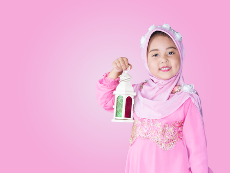 happy muslim girl with full hijab in pink dress , asian traditional style dress playing ramadan lantern.