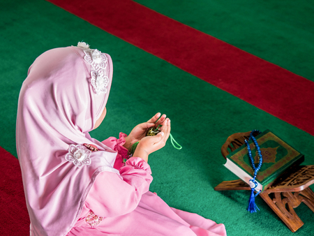 petite fille musulmane: happy muslim girl with full hijab in pink dress , asian traditional style dress , praying  inside the mosque and holy Allah. The text is name of God.