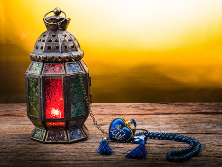candle: Candle light lids on muslim styles lantern shining on arabic letter of the name of God Allah in heart shape, use as greeting on ramadan kareem mubarak Stock Photo