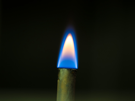 close up shot on flame, hot spot details of fire on black background,  flammability of butane gas for cook and heat concept.