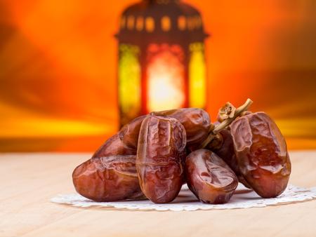 candle: Candle light lids on muslim styles lantern shining on date fruits, use as greeting on ramadan kareem mubarak Stock Photo
