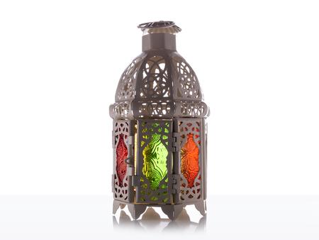 Candle light lids on muslim style's lantern shining on floor with colorful vintage pattern on surface, use as greeting on ramadan kareem mubarak Standard-Bild