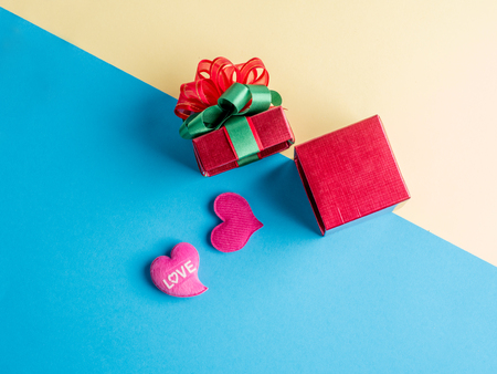 beautiful gift box and red heart on colorful paper background