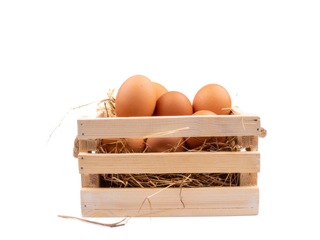 fresh eggs on wooden box with straw on white background