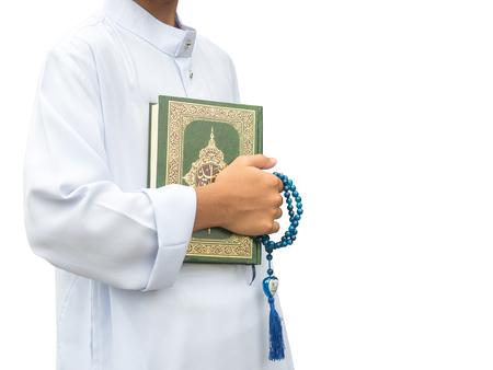 穆斯林男孩拿着真主的圣书,在斋月的夜晚清真寺