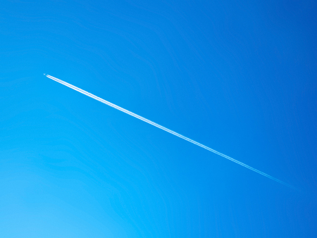long contrail cloud of smoke from jet engine of the airplane over the blue sky Stock fotó