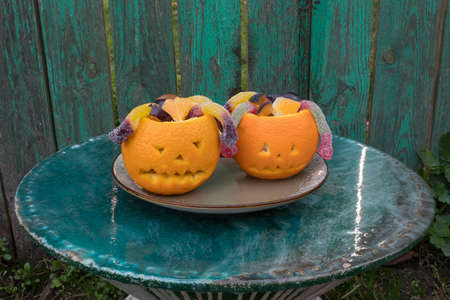Fruit salad for Halloween: orange, plum and candy snakes. Fun kids party. Scary face for Halloween made of orange. Green background.