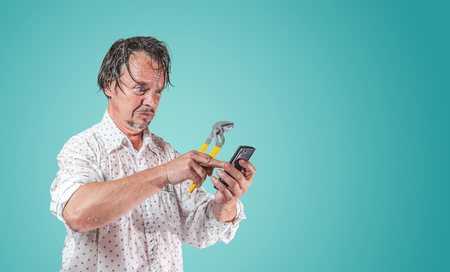 wet man with pipe wrench is looking at smartphone for help