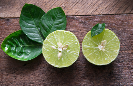 dissect: two lemon dissect with leaves on wood Stock Photo