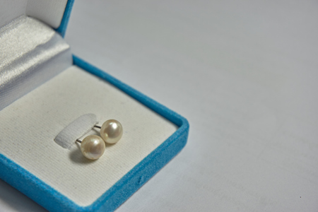 blue velvet: Pearl earring in the blue velvet jewelry box. Close up of a pair of pearl earring