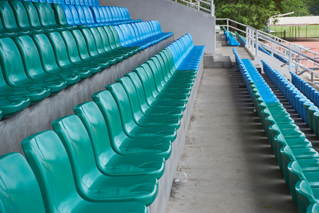 inconsistent: Row of seats in arena. Blue and dark green chairs in a sport stadium.