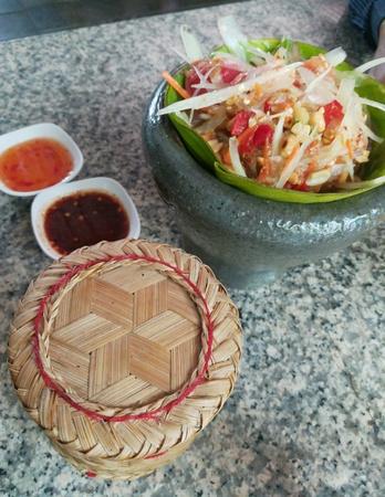 Thai food, Papaya salad and sticky rice in Thai style basket.
