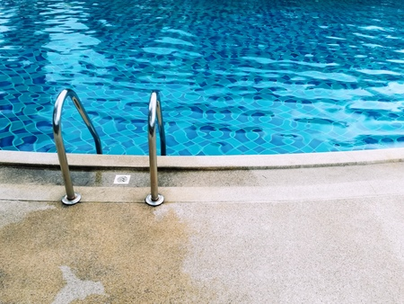 Grab bars ladder in the blue swimming pool. Picture with copy space