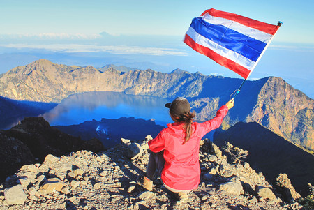 Successful Young Woman Traveler in red cloth, raise her hand and waving Thai flag on top of the mountain peak at Mountain Rinjani, Lombok, Indonesia.
