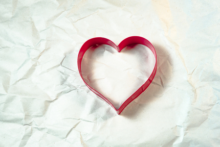 cookie cutter: Cookie cutter,heart shape on the wrinkle white paper background